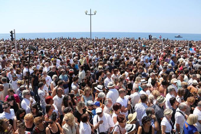 Les gens sont réunis sur la Promenade des Anglais, à Nice, pour une minute de silence en hommage aux victimes de l'attentat qui y a fait 84 morts